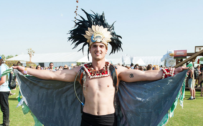 Coachella attendee wearing a traditional Native American headdress, jewelry, and regalia