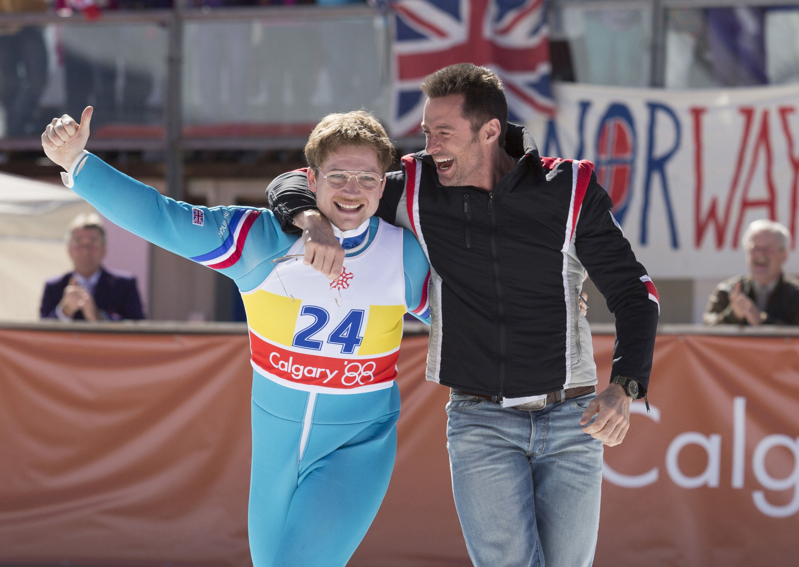 Eddie (Taron Egerton) and his coach Bronson Peary (Hugh Jackman) rejoice in Eddie's triumph. Photo Credit: Larry Horricks. Courtesy of Twentieth Century Fox.