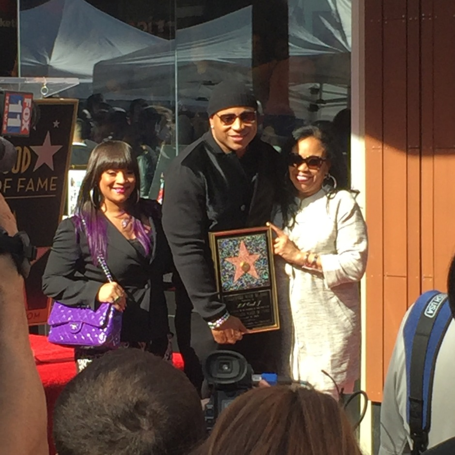 LL Cool J accepts his award accompanied by his wife and mother