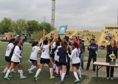 The Jaguars huddle and celebrate around head coach Armando Pelayo as they receive their championship plaque.
