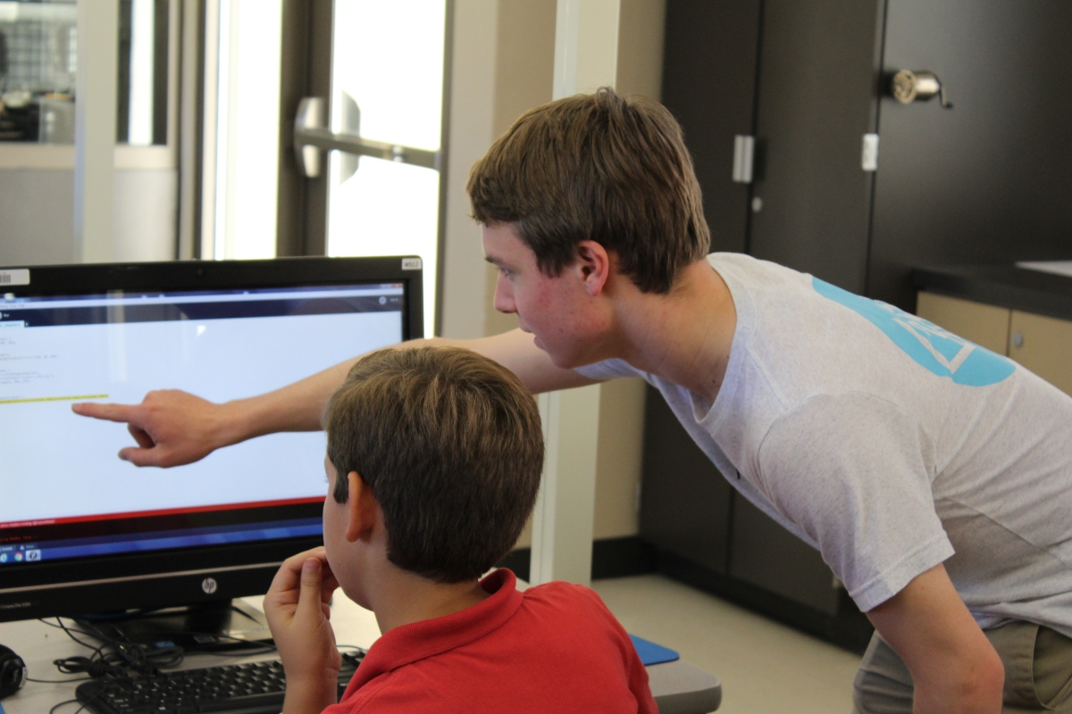 YEP Founder Cole Hersowitz works with a student in coding class at Newport Coast Elementary School.