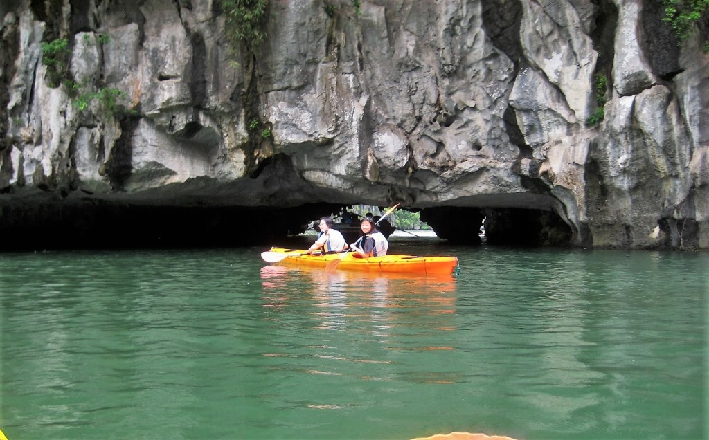 Kayaking through Luon Cave. During high tide, kayakers cannot pass through it.