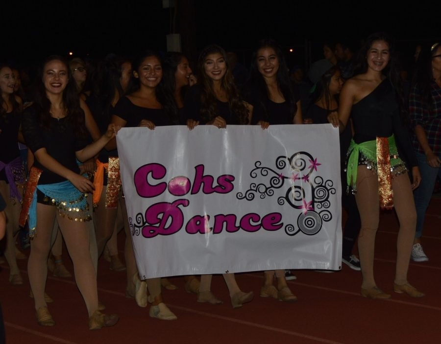 Charter Oak's Advanced Dance Team walk the Homecoming parade in belly dancing outfits