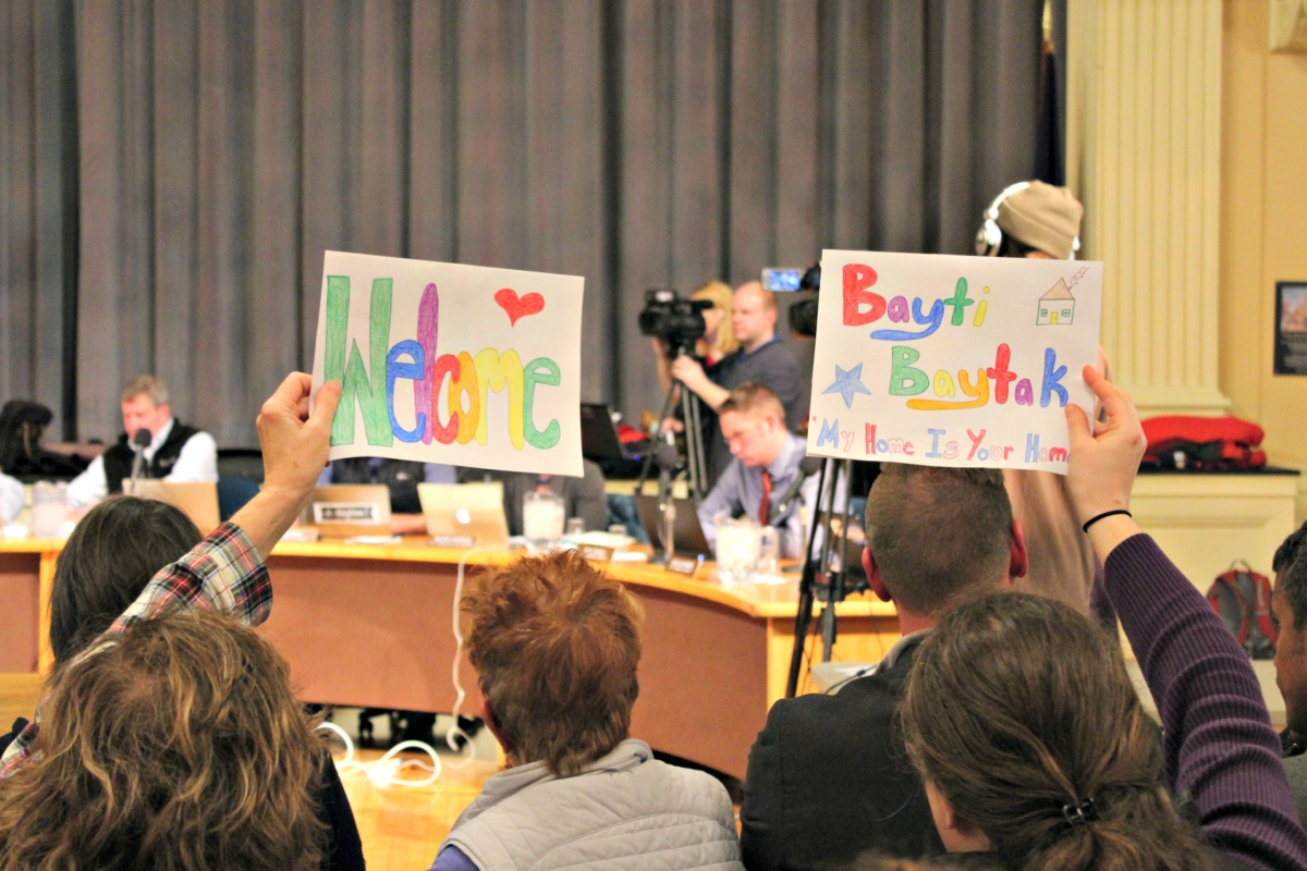 Supporters of a resolution to welcome Syrian refugees in Burlington, Vt. hold handmade signs during a city council meeting on Monday, Nov. 28.