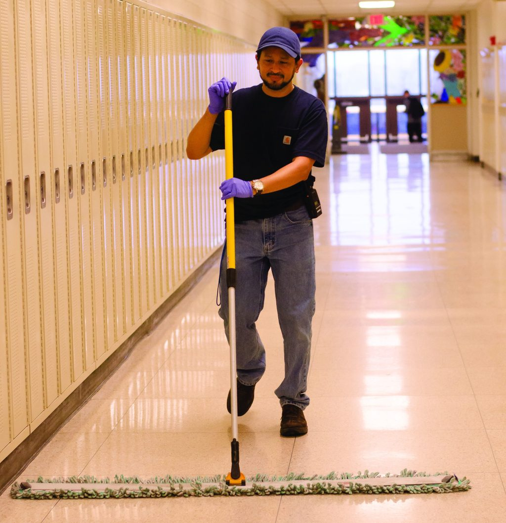 Carlos sweeping the art hallway. Photo by Sarah Longmire
