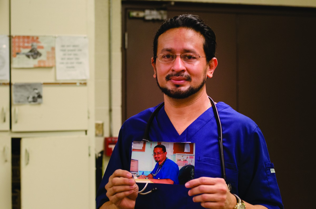 Carlos wearing his scrubs, and holding a photo from when he practiced medicine. Photo by Sarah Longmire
