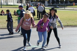 Seniors Sandra Ortega, Nixia Bravo and Nikita Opel run off the street after a group photo on one of the marks depicting the site where JFK was shot. Photo by Rachel Bullock
