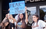 A student from FVHS holds her poster high advocating for the #neveragain movement at the FVPD. Photo by Suzane Jlelati.
