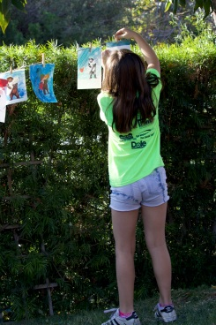 A student hangs her California art with other paintings and drawings. (Photo courtesy of Caelyn Pender)