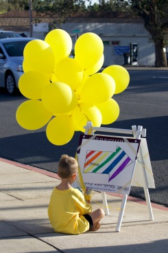 A young student sits near a lemonade stand sign on a nearby street corner. Many volunteers held handmade signs to point passersby in the direction of the lemonade stand. (Photo courtesy ofCaelyn Pender)